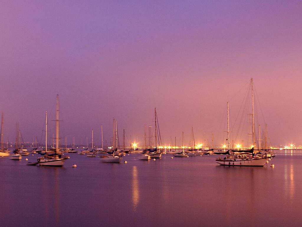Click to get the codes for this image. Sailboats With Purple Sky And Lights, Ocean  Water, Sunsets and Sunrises, Cars Boats Trains etc Background, wallpaper or texture for any blog, web page, phone or desktop